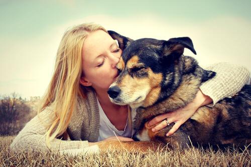 ragazza bionda abbraccia cane che ha eseguito il comando a terra