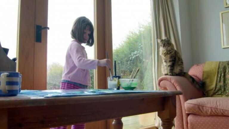 Bambina con gatto in salotto