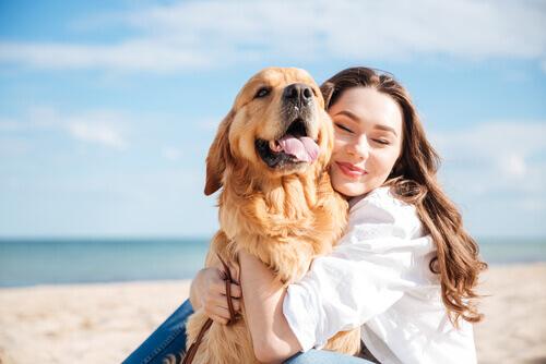 ragazza abbraccia cane in spiaggia
