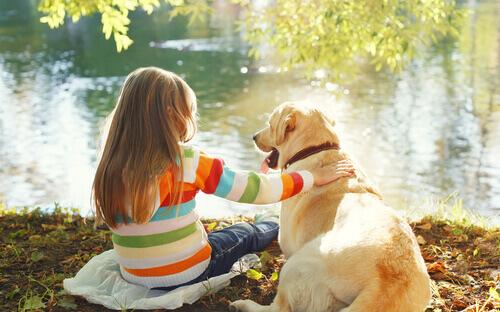 Bambina e cane davanti al lago