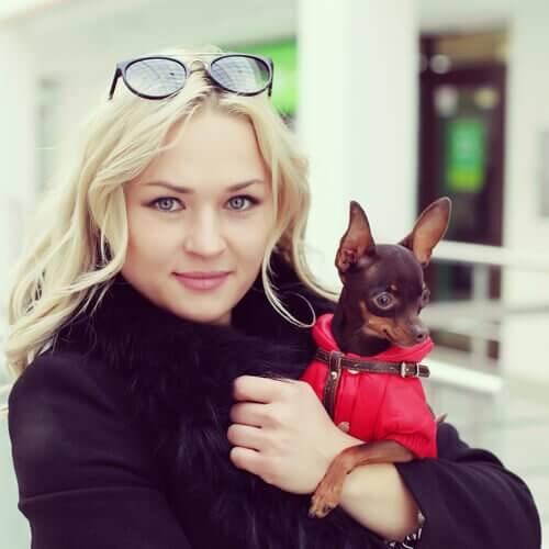 ragazza biona stringe in braccio il suo cagnolino con cappotto