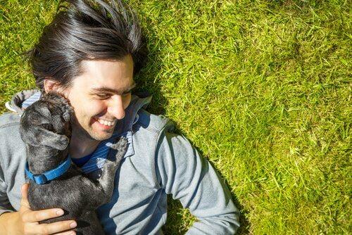 padrone sdraiato sull'erba con cucciolo