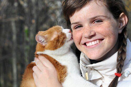 gatto lecca la guancia di una ragazza