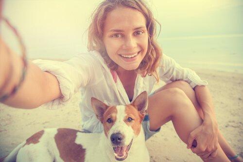 Ragazza si fa un selfie in spiaggia con il cane
