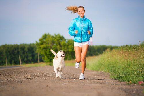 Ragazza sorridente corre con il suo cagnolino bianco
