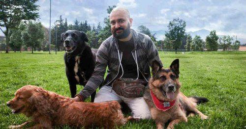 Fisioterapeuta cinofilo con tre cani su un prato