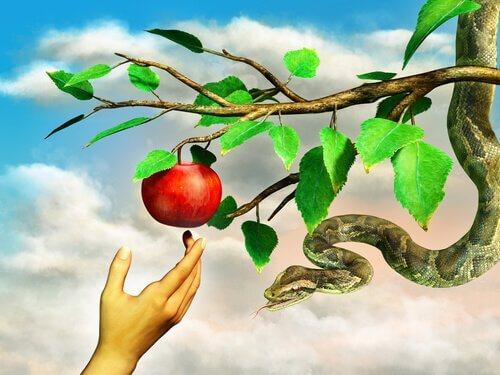 Mano afferra la mela dell'eden con il serpente