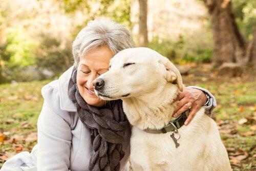Anziana abbraccia il suo cane in un parco