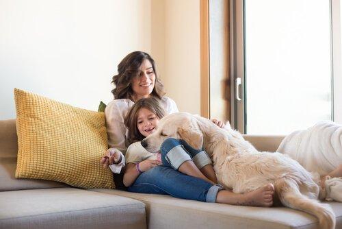 Madre e figlia sul divano col cane