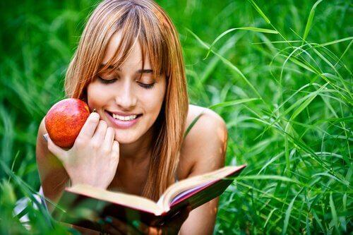 Ragazza legge un libro su un prato con una mela in mano