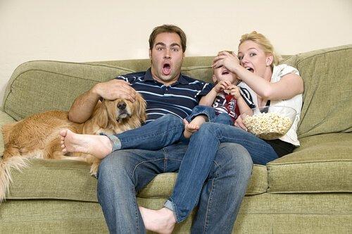 una famiglia sul sofà col cane guarda un film