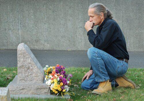 Uomo in ginocchio davanti alla tomba del cane