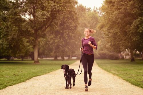 Donna che corre con cane al parco
