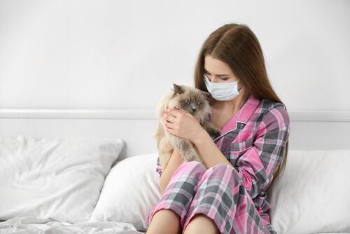 Donna con mascherina e gatto