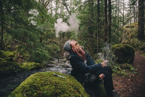 Donna che fuma nella foresta