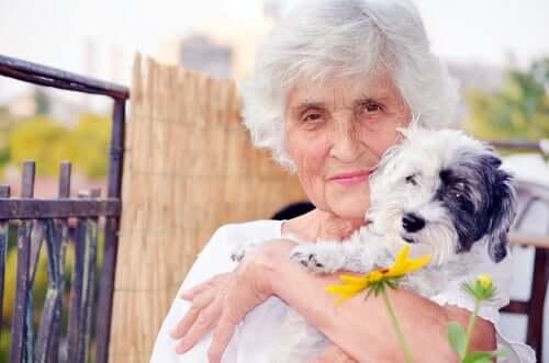 Donna anziana che ha deciso di prendere un cane e lo abbraccia