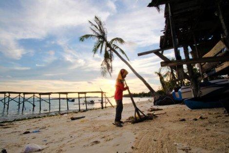 Ragazza pulisce una spiaggia