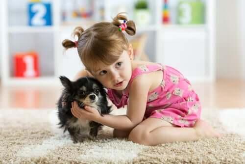 Bambina in casa con un cane