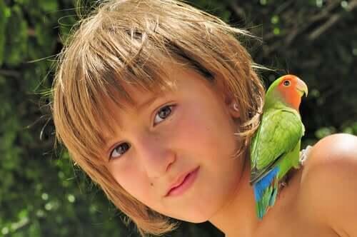 Bambina con un pappagallo sulla spalla