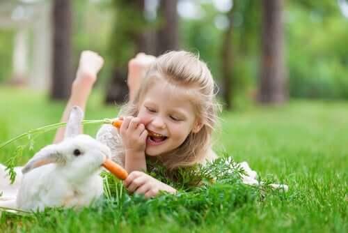 Bambina che mangia le carote con un coniglio.