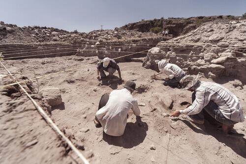 Archeologi scavano in un sito assolato.