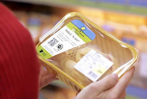 Persona che compra al supermercato del pollo confezionato con il codice QR.